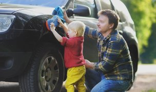 Young boy and his dad washing new car
