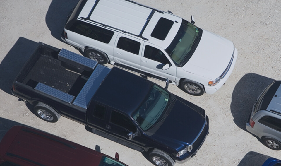 Birdseye view of carpark with a navy ute and white car