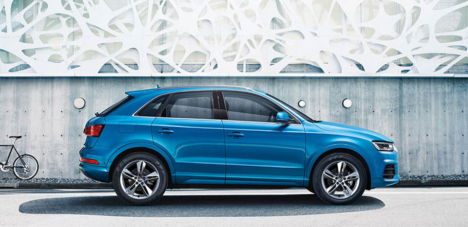 Blue Audi Q3 Hatch parked in front of artistic building