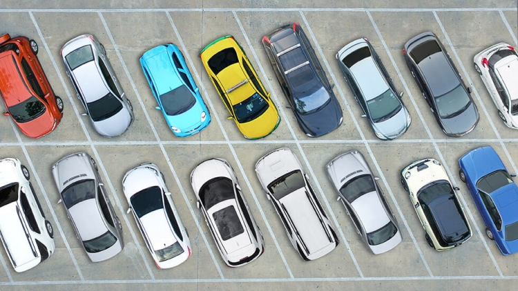 Birdseye view of carpark with two rows of coloured vehicles