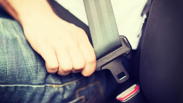 Close up of driver sitting in vehicle fastening seatbelt