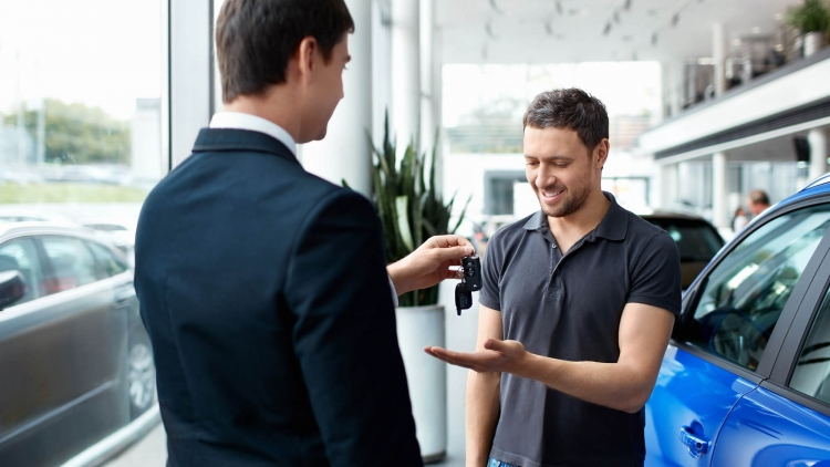 Happy man receiving the keys to his new car in showroom from the sales rep